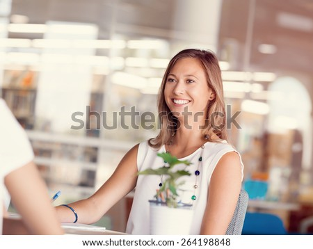 Happy and confident young woman in an office