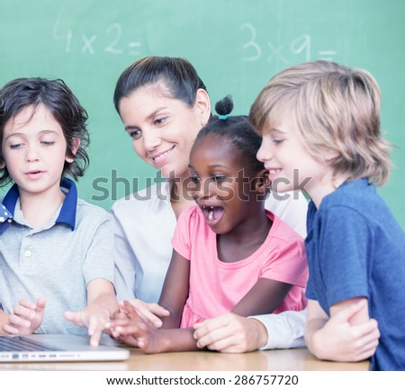 Happy and curious multiracial elementary students learning to use computer with teacher.