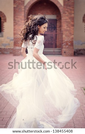 Happy and delicate bride running in her wedding day, in front of the church - stock photo