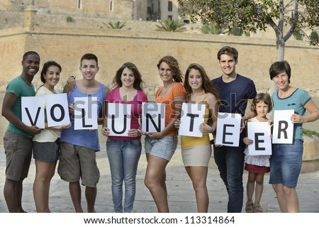 happy and diverse volunteer group holding sign - stock photo