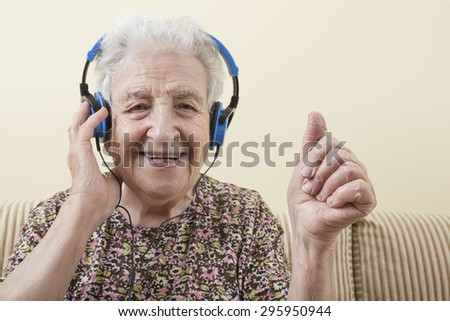 happy and energetic senior woman listening music with headphones - stock photo