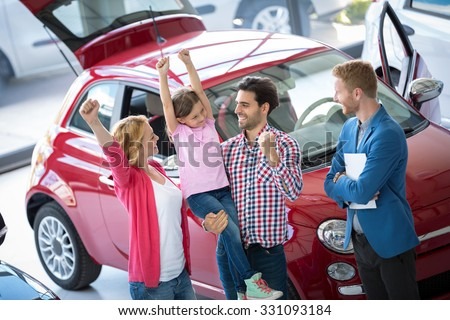 Happy and excited family celebrating just bought a new car from dealership - stock photo