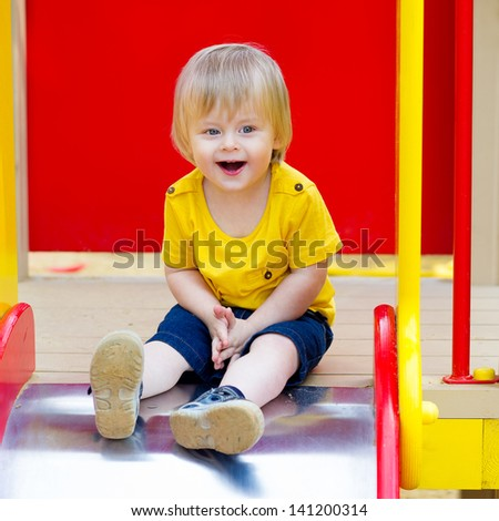 Happy and excited toddler on the slide - stock photo