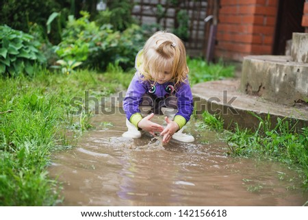 Happy and funny baby girl playing in puddles - stock photo