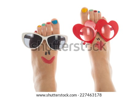 Happy and funny caucasian summer feet with colorful nail polish and sunglasses - stock photo