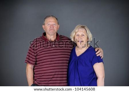 Happy and healthy senior couple looking at camera, studio shot over grey background. - stock photo