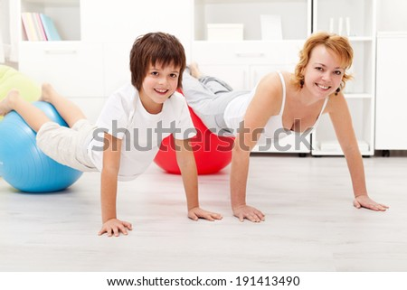 Happy and healthy woman exercising on large gymnastic balls with her son at home - stock photo