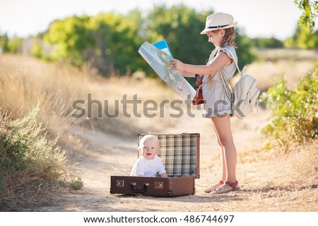 happy and joyful children with  suitcases on road.vacation and trip concept. freedom and wind. girl and boy travelers. holidays, voyage, nature on background. summer time. boyscout