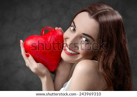 Happy and joyful young woman holding red heart on grey background in studio. Happy valentines greeting concept - stock photo
