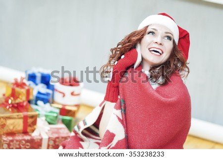 Happy and Laughing Caucasian Santa Girl with Lots of Presents Behind. Talking by Cellphone and Sitting Under the Plaid Indoors. Horizontal Image Composition