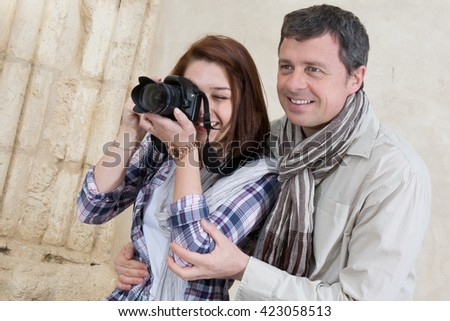 Happy and lovely tourists taking photo of something