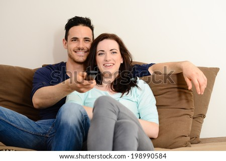 happy and lovely  young couple at home in sofa watching tv together - stock photo