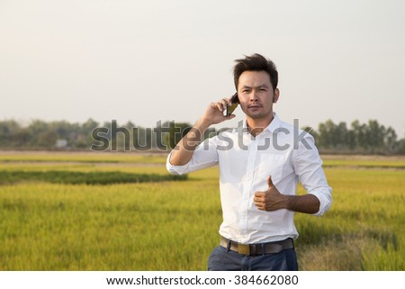 happy and Relaxation businessman use a telephone standing on the rice green field - stock photo