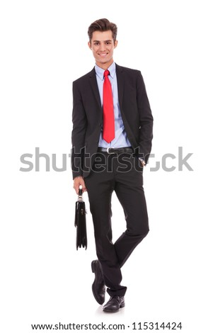 happy and relaxed business man standing with his hand in his pocket and holding a briefcase, looking at the camera - stock photo