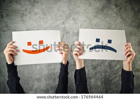 Happy and sad face, emoticons. Women holding papers with happy and sad emoticons. - stock photo