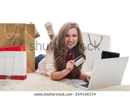 Happy and satisfied shopping girl using laptop and holdinf credit or debit card surrounded by shopping bags - stock photo