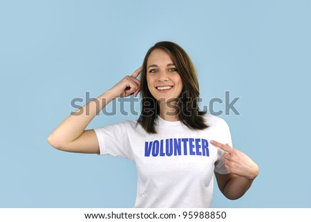 Happy and smart volunteer girl on blue background - stock photo