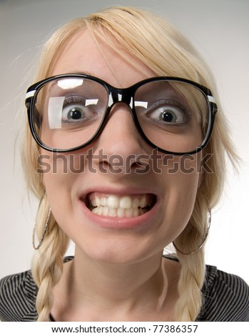 Happy and smart young blond woman with funny glasses and plait looks like nerdy girl. Smiling and looking at camera, humor style on white background. - stock photo