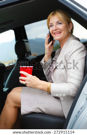 Happy and smile old senior woman 60-65 years with white teeth talking by mobile cell phone in the back of a car and holding plastic glass in hand.