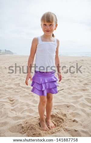 Happy and smiling barefoot young girl in purple skirt and white top at beach