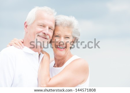 Happy and smiling couple in front of cloudy sky - stock photo
