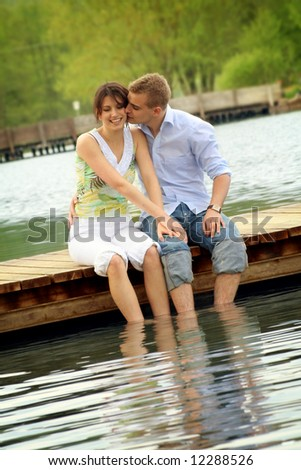 happy and smiling couple sitting on a bridge in front of a lake - stock photo
