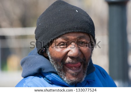 Happy and smiling homeless african american man outdoors during the    Happy Homeless Man