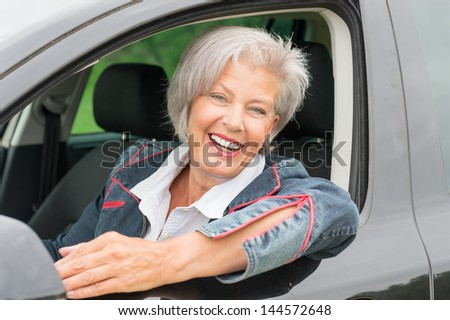 Happy and smiling senior woman in black car - stock photo