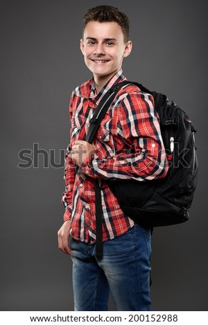 Happy and smiling teenager student with backpack on gray background - stock photo