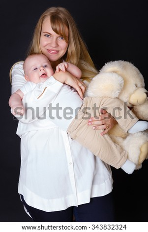 Happy and smiling Young mother holding on hands Baby boy 4 month old and teddy bear on black background. Concept happy family