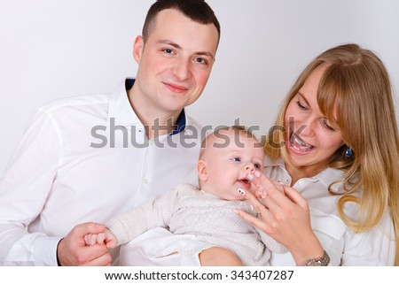 Happy and smiling Young Parents playing With Their Baby boy 4 month old on white background. Concept happy family