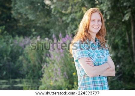 Happy and smiling young woman poses for a summer outdoor portrait in nature with folded arms and looks at the camera.
