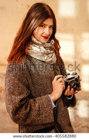 happy and stylish pretty hipster woman holding film photo camera and smiling on background of old red wall in European city