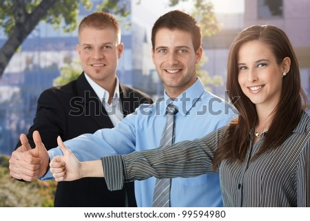 Happy and successful business team giving thumb up, outdoor portrait.