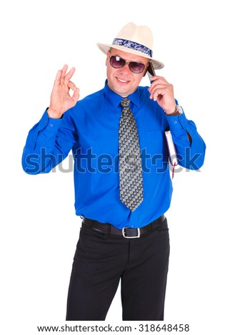 Happy and successful businessman in blue shirt, tie, sunglasses and white hat. Speaking by cell mobile phone, holding notebook under his arm and show gesture Ok. Isolated white background - stock photo