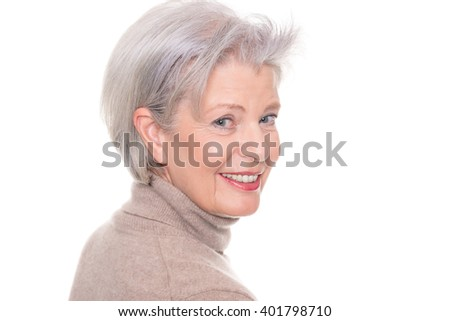 Happy and successful senior woman with pullover in front of white background - stock photo
