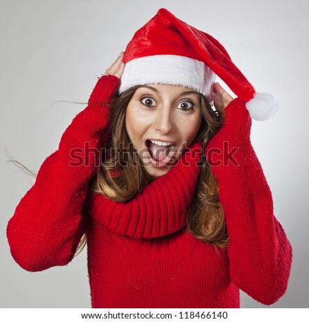 Happy and surprised beautiful Christmas woman. Young christmas woman wearing a santa hat. Isolated - stock photo