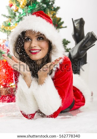 Happy and surprised lovely young lady wearing Christmas costume enjoying the falling snow while lying on the ground. - stock photo