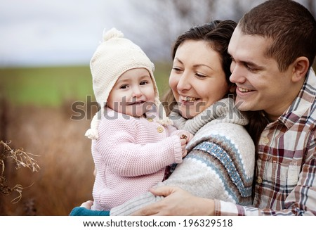 Happy and young family relaxing together in autum nature - stock photo