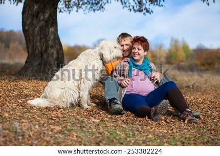Happy and young pregnant couple hugging in nature - stock photo