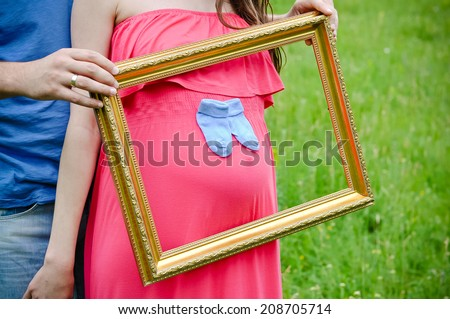 Happy and young pregnant couple outdoors with photo frame - stock photo