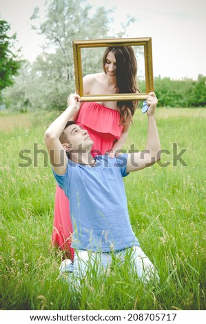 Happy and young pregnant couple outdoors with photo frame