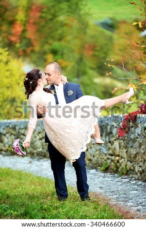 Happy and young wedding couple. Groom carrying his beautiful bride on arms on a small mountain path with colored autumn background. Beautiful couple looks into the eyes after their marriage. - stock photo
