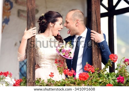 Happy and young wedding couple head to head joking and sticking out the tongue. Crazy couple of lover touching foreheads and having fun after their marriage, side view.