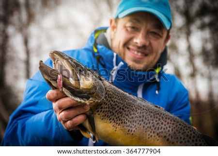 Happy angler with brown trout - stock photo