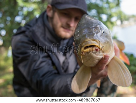 Happy angler with carp fishing trophy.