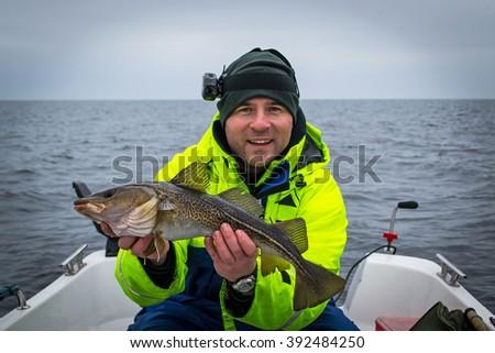 Happy angler with fresh caught cod fish - stock photo