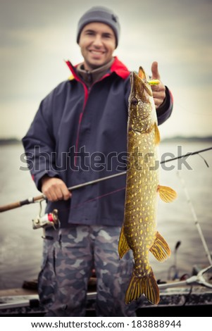 Happy angler with pike fishing trophy  - stock photo
