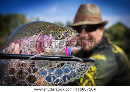 Happy angler with trout loach  - stock photo