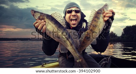 Happy angler with zander fishing trophy - stock photo